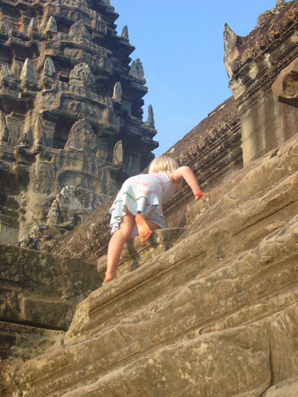 A challenge for the girls climbing up the steep, worn steps to the central gallery of Angkor Wat. The world's largest religious building.