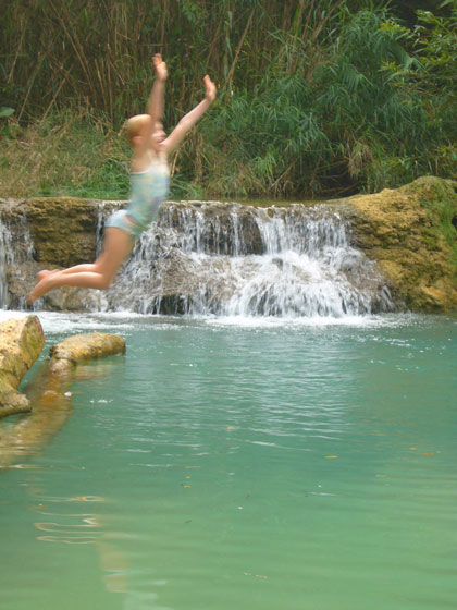 Ella jumps from the lime encrusted fallen tree into one of the many swimming holes downstream from the Kuang Si waterfall.
